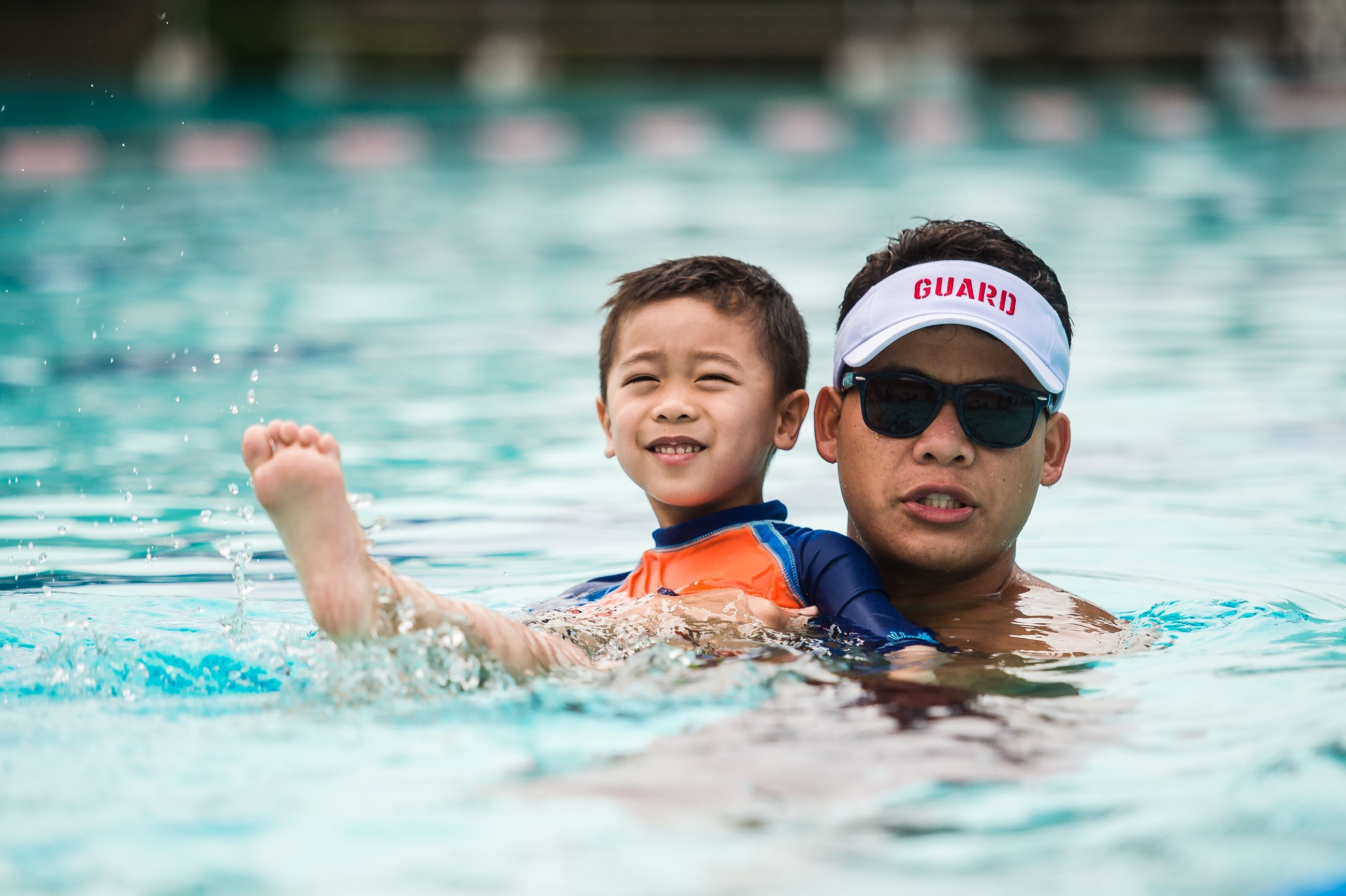 Lifeguard with child in swimming pool