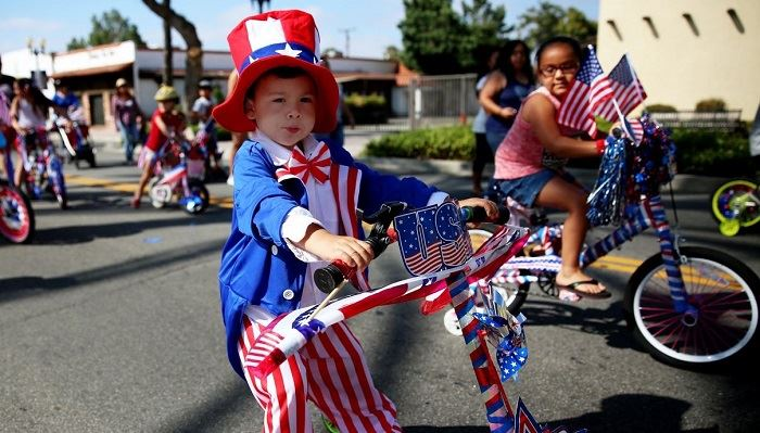 Little boy dressed as Uncle Sam on bicycle in event parade.