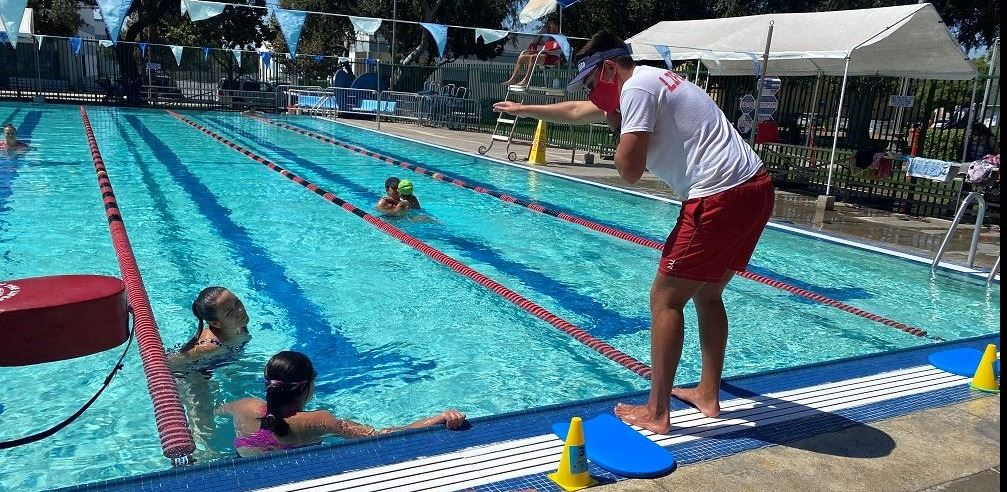 Swim Instruction 2020 - Photo of lifeguards teaching a child how to swim.